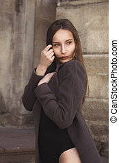 Lovely young woman in a coat at the city