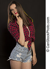 Lovely young woman in jeans shorts and plaid shirt