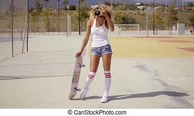 Lovely young woman posing with a skateboard