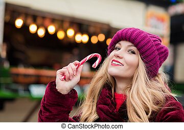 Lovely young woman posing with Christmas candy cane at the street