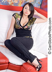 Lovely young woman sitting on a sofa
