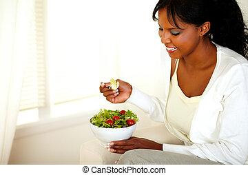 Lovely young woman smiling and looking to salad
