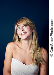 Lovely young woman smiling on dark background