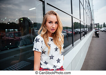 Lovely young woman with long blonde hair standing