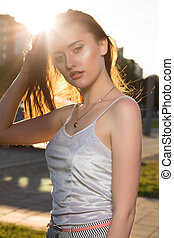Lovely young woman with natural makeup posing in rays of sun at avenue
