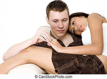 A young man and woman sitting together on a sofa/couch
