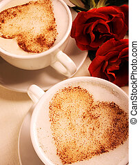 Two cups of coffee with heart design on top.