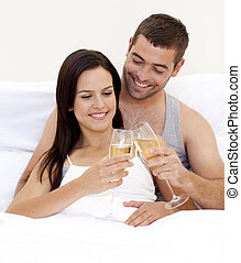 Lovers drinking champagne in bed