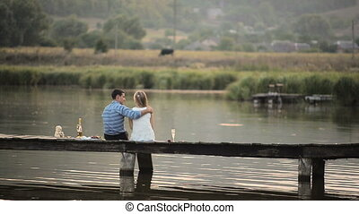 lovers drinking champagne on the lake