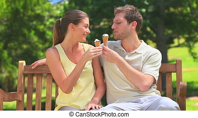 Lovers eating ice creams on a bench
