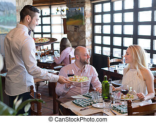 Lovers eating salads in restaurant