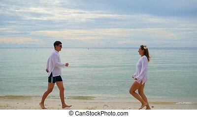 lovers guy and girl run towards each other along the beach
