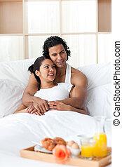 Lovers having breakfast lying on the bed