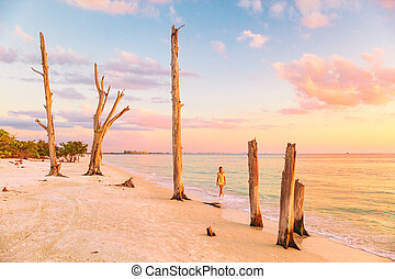 Lovers key beach in the gulf of Mexico, Florida travel destination. Woman relaxing watching sunset walking in ocean water on american beach. Southwest Florida