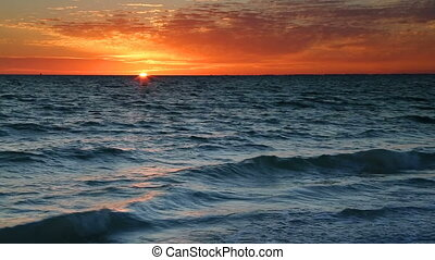 Colorful loop features the sun setting over breaking waves on the Gulf of Mexico at Lovers Key State Park near Ft. Myers, Florida.