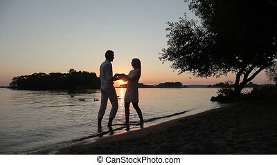 Lovers kiss on the sunset by the water.