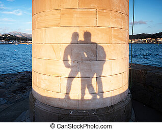 Lovers play with their shadows on  Lighthouse wall,
