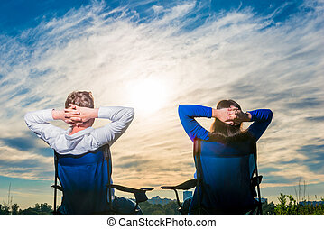 lovers sit on the chairs and look at the beautiful morning sky
