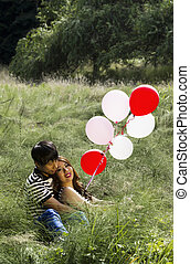 Lovers with their balloons resting in Tall Green Grass Field