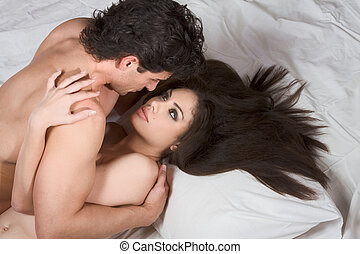 Loving affectionate nude heterosexual couple on bed making...