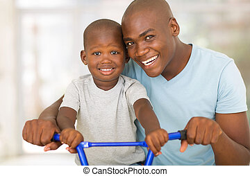 african american father teaching son to ride a bicycle