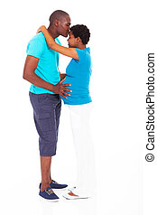man kissing pregnant wife isolated