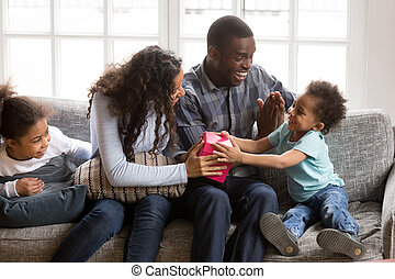 Loving african family sitting on couch at home