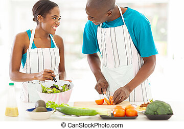 african husband and wife cooking dinner together