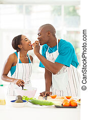 african husband feeding wife a piece of tomato
