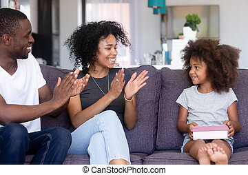 Loving african parents clap hands congratulating little daughter happy birthday