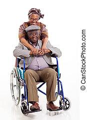 loving african wife hugging disabled husband