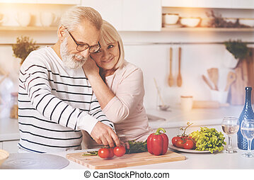 Loving aged couple resting in the kitchen
