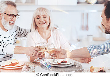 Loving aged parents enjoying meal with their adult son