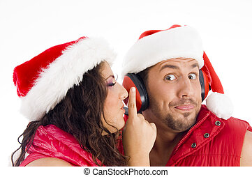 loving american couple wearing christmas hat and woman shushing
