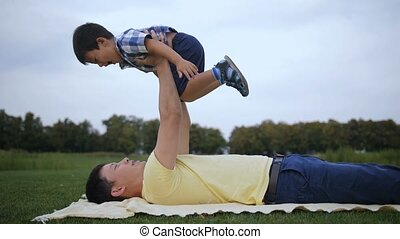 Loving asian father lifting up his laughing boy