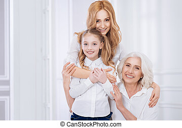 Loving beautiful woman embracing her little girl and senior mother