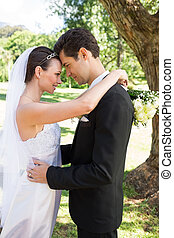 Loving bride and groom embracing in garden - Profile shot of...