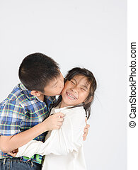 Loving brother and little sister hugging on gray background.