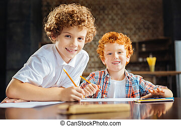 Loving brothers drawing together and smiling