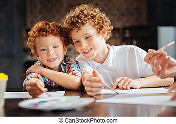Loving brothers painting together at table