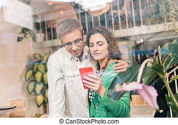 Loving caring man hugging his beautiful wife showing him some photos