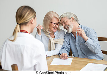Loving caring senior aged couple laughing signing documents at m