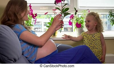 Loving child girl give pregnant mother flower and hug kiss...