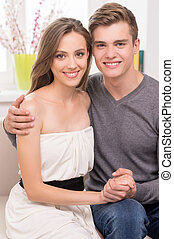 Loving couple at home. Beautiful young couple hugging and smiling while sitting on the couch
