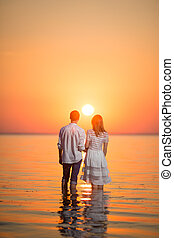loving couple at sunset in the water
