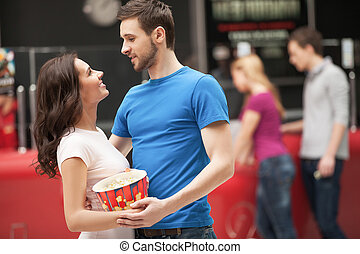Loving couple at the cinema. Cheerful young couple hugging and looking at each other while standing at the cinema hall