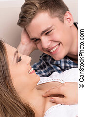 Loving couple. Beautiful young couple lying close to each other and smiling