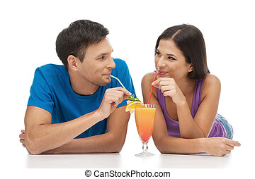 Loving couple. Beautiful young loving couple drinking cocktails and looking at each other while isolated on white