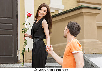 Loving couple. Beautiful young loving couple holding hands and looking at each other