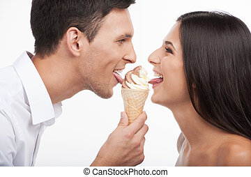 Loving couple. Beautiful young loving couple looking at each other and eating ice-cream while isolated on white